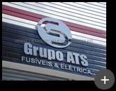 Letreiro em aço inox escovado com logotipo no formato circular e letra S representando a empresa do Grupo ATS - Fusíveis & Elétrica.