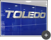Letreiro inox escovado instalado em ambiente interno para a indústria Toledo
