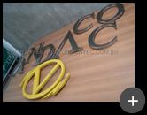 Letreiro de aço inox escovado com logotipo na cor amarela para empresa de moda Andacco do grupo Cacique