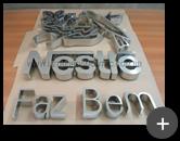 Letreiro da Nestlé em aço inox escovado com logotipo conforme a identidade visual da empresa Nestlé sendo produzido