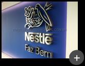 Letreiro Nestlé de aço inox escovado com logotipo instalado em ambiente interno