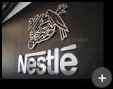 Letreiro da indústria Nestlé em aço inox polido com logotipo e letras conforme as características da Nestlé.
