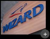 Letras para escola Wizard galvanizadas com pintura e detalhes em vermelho no logotipo, prontas para instalação na fachada da escola de idiomas