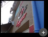 Letreiro galvanizado da cafeteria instalado na fachada em ambiente externo da lanchonete