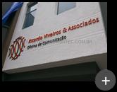 Letreiro com logotipo em formato geométrico nas cores laranja e cinza produzido em aço galvanizado para Oficina de Comunicação Ricardo Viveiros