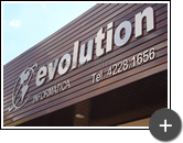 Letreiro de aço inox polido com letras e logotipo com formas circulares e desenho do mapa mundi produzido em inox com sofisticação para a loja Evolution Informática