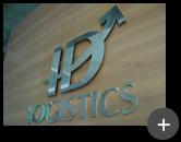 Letreiro com letras de inox polido e logotipo com formato de flecha conforme a comunicação visual da empresa HD Logistics