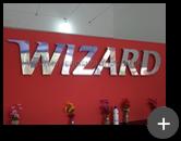 Letreiro de aço inox polido com alto brilho instalado em ambiente interno na escola Wizard