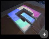 Letreiro de acrílico iluminado com leds, parte frontal com impressão digital projetando a luminosidade para frente no ambiente