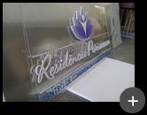 Letreiro com placa em acrílico cristal com letras em acrílico branco recortadas a laser e logotipo produzido com impressão digital. Residência Primaveras - clínica de repouso