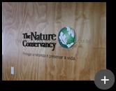 Letreiro de acrílico com pintura na cor preto fosco e logotipo com adesivo em impressão digital em formato circular representando o setor do meio ambiente da empresa - The Nature Conservancy