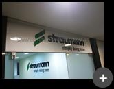 Letreiro instalado no escritório em acrílico preto e logotipo com adesivo sobreposto na cor verde impactando o visual da empresa com sofisticação