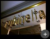 Letreiro da fachada das redes de lojas de roupas da Rubinella em latão polido instalado