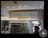 Letreiro da loja CNS de calçados em aço inox polido e iluminado por leds em ambiente interno