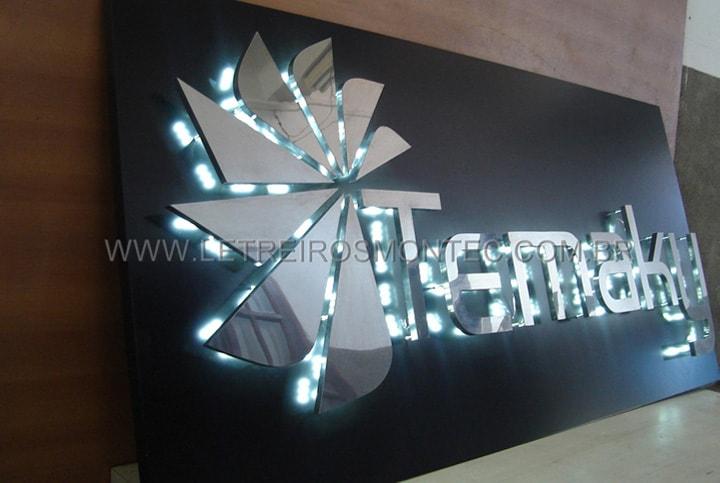 Letreiro de led com iluminação contornando as letras na fachada do restaurante com logotipo geométrico